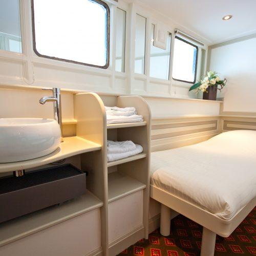 Wastafel en comfortabel hotelbed